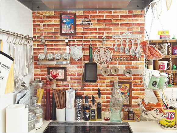 ブリック調の壁紙とキッチンツールがとてもにぎやかなキッチン。