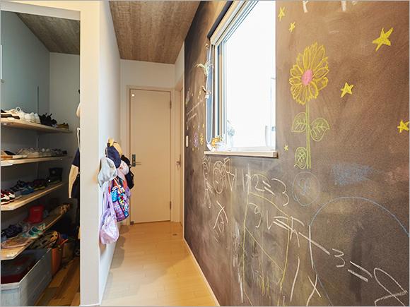 玄関を入ると黒板の壁紙に描かれたお子さんの絵がお出迎え