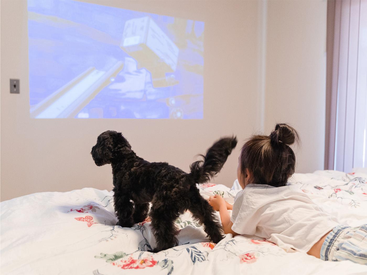 プロジェクターがついている寝室でお気に入りのアニメを観る娘さんと愛犬のオレオ。