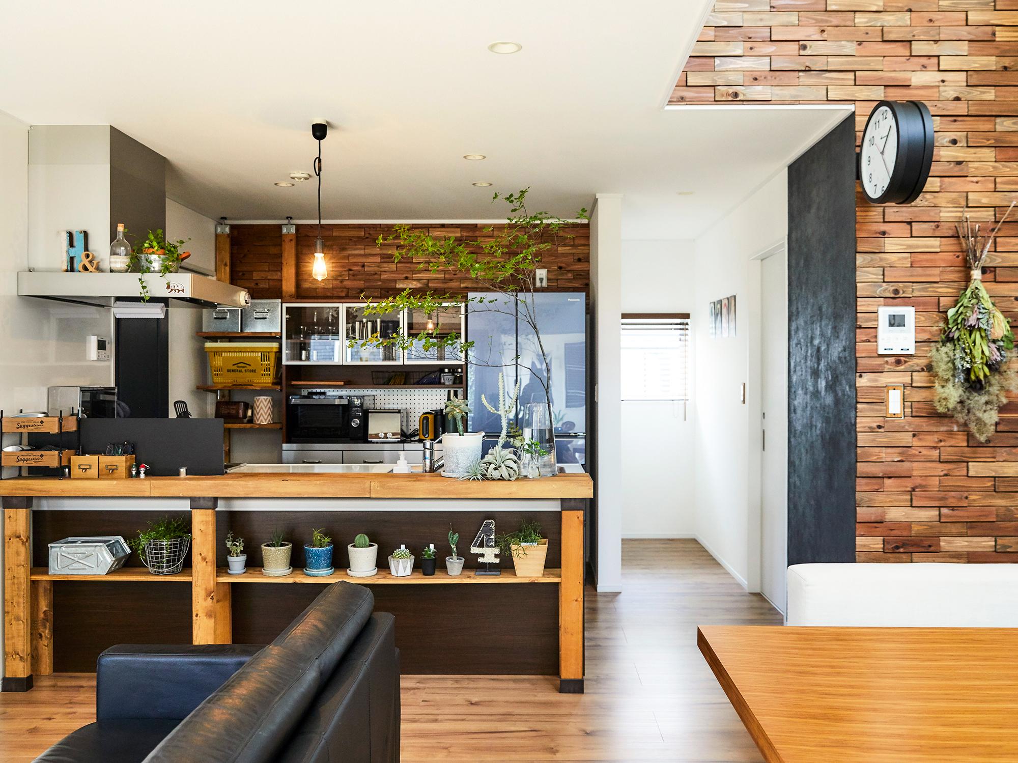キッチンカウンターは木材でカバーし、棚をディアウォールで制作。味わいのある壁の木ブロックは、後からDIYを加えたもの。