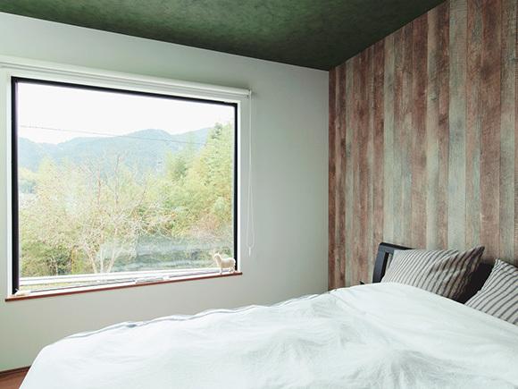 寝室は緑と調和する落ち着いたウッド調に。