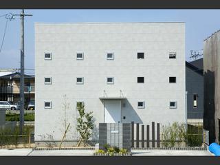 重圧なコンクリート外壁に、小窓がリズムを奏でる家